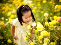 Young girl smelling a flower.